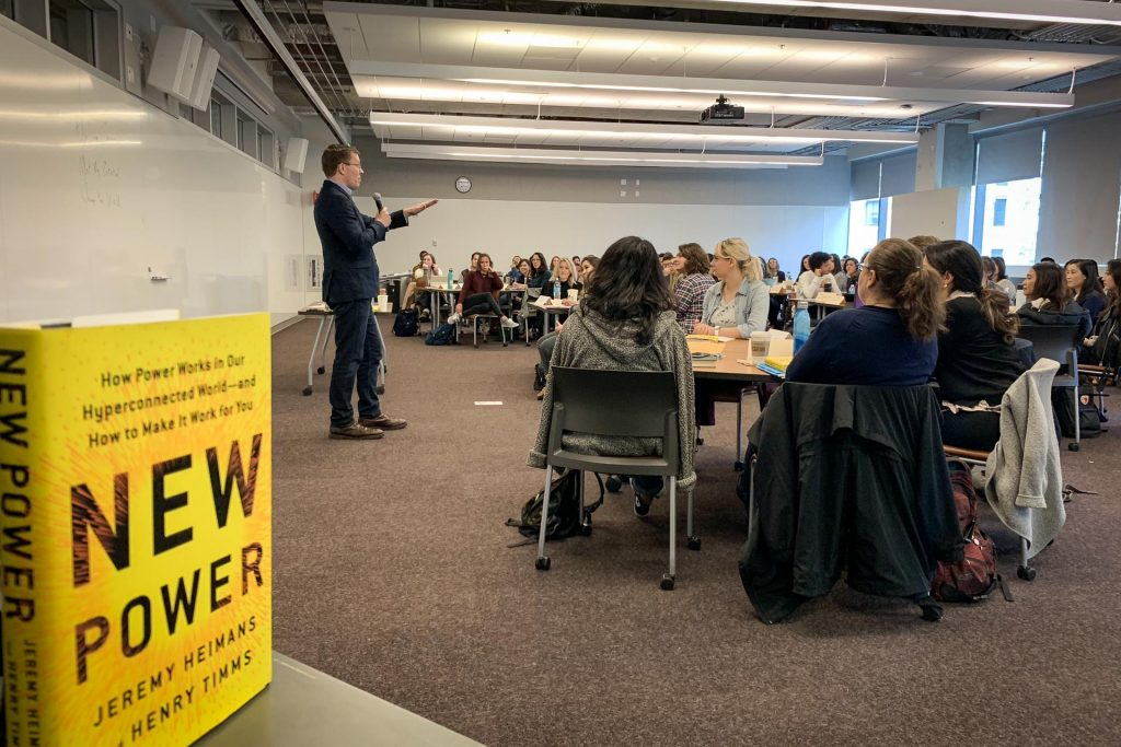 Henry Timms holding microphone addresses room full of seated Comm Lead students, with yellow New Power book in the foreground.