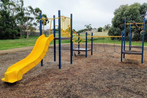 A play structure, including a yellow slide, climbing ladder and chain bridge, over woodchips. Grass and trees in the background.