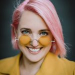 Headshot of a female-presenting person w pink hair, yellow tinted glasses and light skin.